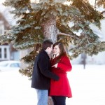 snowy winter engagement pictures against pine tree in bloomington minnesota