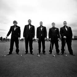Black and White wedding photograph of groomsmen on golf course