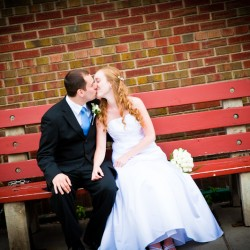 Bride and Groom kissing on bright red bench in Hudson Wisconin wedding photograph