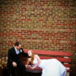Bride and Groom on a bright red bench in Hudson Wisconin wedding photograph