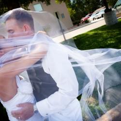 Bride and groom kissing under wedding veil