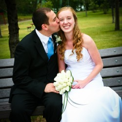 Groom kissing bride on her cheek sitting on park bench in Hudson Wisconsin