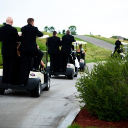 Wedding photograph of bridal party driving golf carts at the Tournament Players Club in Blaine MN