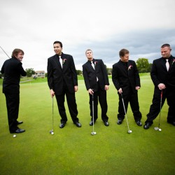 Wedding photograph of groom and groomsmen on golf course having fun