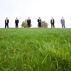 Wedding photographs of groom and groomsmen at Church of the Open Door in Maple Grove MN in the grass