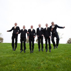 Wedding photographs of groom and groomsmen at Church of the Open Door in Maple Grove MN jumping